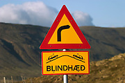 Road sign in rural Iceland warning of a blind hillcrest on a curve.