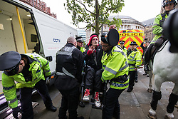 © Licensed to London News Pictures . 01/10/2017. Manchester, UK. Police arrest a wheelchair user who pushes off a policeman's hat as she is lifted in to a police van , amongst anti Tory protesters blocking tramtracks at St Peter's Square opposite the Midland Hotel . People take part in a demonstration against the Conservative Party in Manchester during the Conservative Party Conference , which is taking place at the Manchester Central Convention Centre . Photo credit: Joel Goodman/LNP