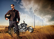Lifestyle portrait of a man posing with his motorcycle in a giant field with windmills towering above him.