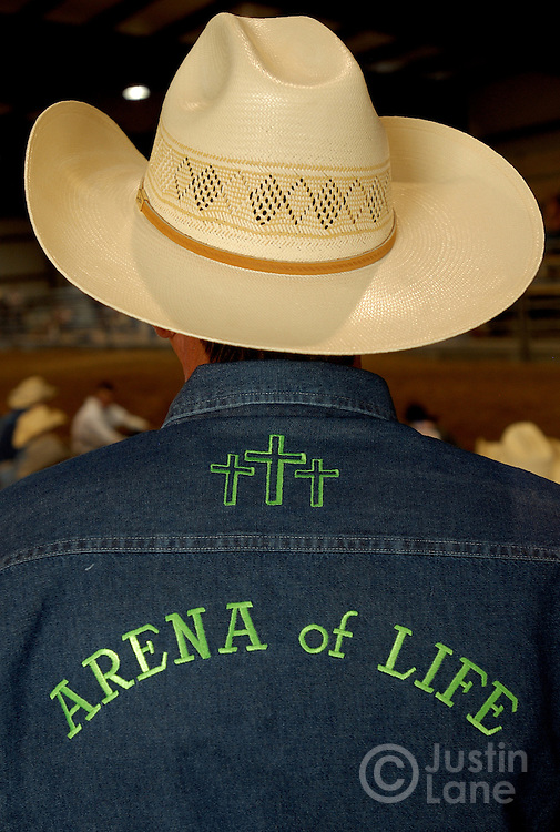 A volunteer's back is seen during the Christian rodeo held each Thursday by the Cowboy Church in Amarillo, TX in their own arena, the Arena of Life, behind the church, Thursday July 14, 2005. The church rodeo, in which semi-professional bull riders compete, is designed to bring in people who are interested in the sport then expose them to the teachings of Jesus.