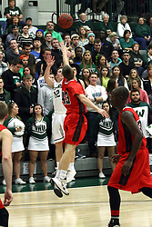 10 January 2015:  Joel Pennington launches a 3 point attempt guarded by Mike Leazer during an NCAA mens division 3 CCIW basketball game between the Carthage Reds and the Illinois Wesleyan Titans in Shirk Center, Bloomington IL