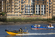 A Thames Rib Experience pleasure speedboat drives upstream, pasing a small barge and riverside residential apartment properties in Wapping, on 17th January 2020, in London, England.