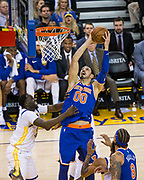 New York Knicks center Enes Kanter (00) takes the ball to the basket over Golden State Warriors forward Draymond Green (23) at Oracle Arena in Oakland, Calif., on May 2, 2017. (Stan Olszewski/Special to S.F. Examiner)