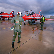 Squadron Leader Duncan Mason of the elite 'Red Arrows', Britain's prestigious Royal Air Force aerobatic team, strides out across a gloomy, rainswept 'apron' at RAF Scampton, Lincolnshire. Squadron Leader Mason will fly up to 6 times daily during winter training ,when weather permits, learning new manoeuvres. Wearing winter green flying suits, their day is spent flying and de-briefing. Mason  wears a green flying suit with anti-g pants and helmet on with its pilot number. He is being greeted by a member of the team's support ground crew who outnumber the pilots 8:1.  The engineer wears a fluorescent yellow tabard and stands politely by the waiting aircraft on the 'line'. He has already prepared it for flight and helps with any technical issues that may arise.