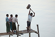 One man swings a big hammer on a post, while three others observe, Chindwin Riverbank