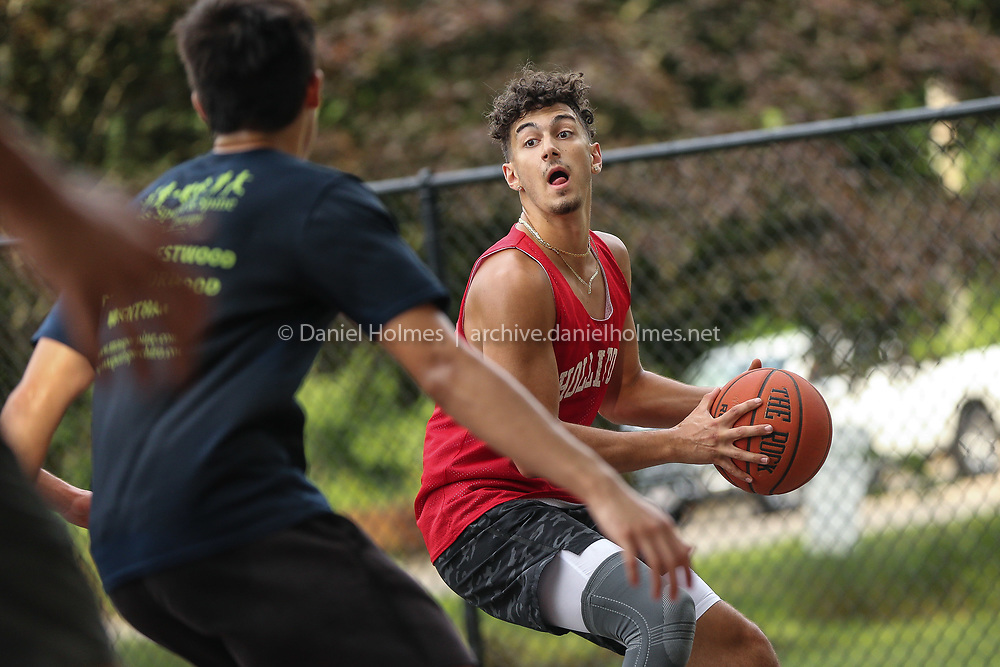 (7/24/20, MILLIS, MA) Holliston's Zak Latifi (Regis College) looks for an open teammate during a pickup game at the Exchange St. basketball court in Millis on Friday. [Daily News and Wicked Local Photo/Dan Holmes]