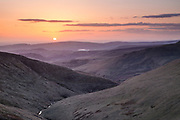 Views over Doctor's Gate looking west towards Glossop. Stunning sunset colours enhanced by volcanic ash from Iceland. Spring in the dark peak, Derbyshire, Peak District National Park, England, UK.