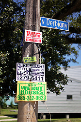 26 August 2015. New Orleans, Louisiana. <br /> Hurricane Katrina revisited. <br /> Rebuilding the Lower 9th Ward ten years after the storm.. <br /> Signs nailed to a street post near brad pitt inspired 'make it Right' homes on Tennessee Street.<br /> Photo credit©; Charlie Varley/varleypix.com.