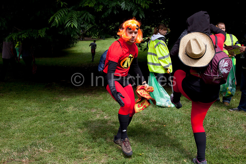 London, UK. Tuesday 7th August 2012. Men's Triathlon held in Hyde Park. Fans of the event gather to watch in various outfits and guises. These super heroes dressed up Hit Girl as are fans of team Spain.