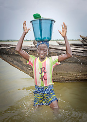 © Licensed to London News Pictures. 05/07/2013. Koulikoro,  Mali.  Mamouna (12) lifts a heavy bucket of sand onto her head in the river Niger.  She will spend 8 hours a day dredging sand which has been dropped by the workers.  The sand is transported to the shore which is then delivered across Mali for use within the construction industry.   Photo credit: Alison Baskerville/LNP