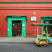 Street vendor pushing his cart past a Spanish Colonial building in Oaxaca, Mexico