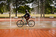05 AUGUST 2020 - DES MOINES, IOWA: A child rides a bike through a splash pad in Evelyn K. Davis Park in Des Moines.     PHOTO BY JACK KURTZ