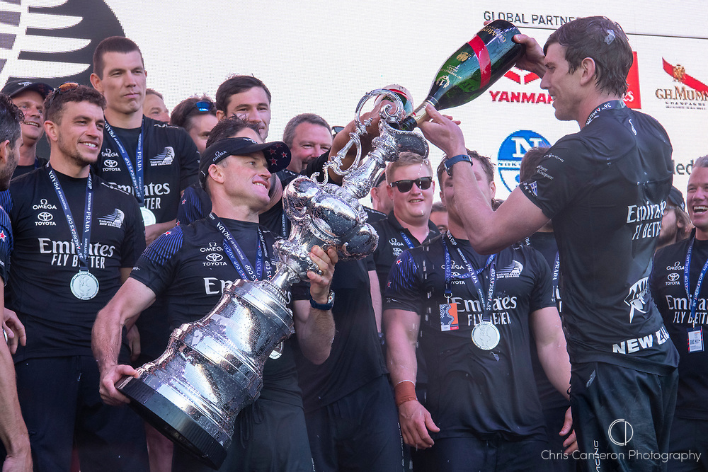Emirates Team New Zealand celebrate on stage after being presented with the Americas Cup on stage after beating Luna Rossa Prada Pirelli Team 7 - 3. Peter Burling fills the America's Cup with Champagne.  Wednesday the 17th of March 2021. Copyright photo: Chris Cameron