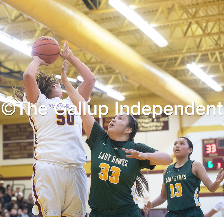 Tohatchi Cougar Montana Soto (50) takes a shot in the paint as Thoreau Hawk DeAnn Howe (33) defends Tuesday night at Tohatchi High School in Tohatchi. Tohatchi beat Thoreau 51-46.