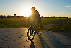© Licensed to London News Pictures 26/02/2021.        Blackheath, UK. A cyclist on the Common. People get out of their homes from a third national Coronavirus lockdown to enjoy some bright sunny weather on Blackheath Common, London. Photo credit:Grant Falvey/LNP