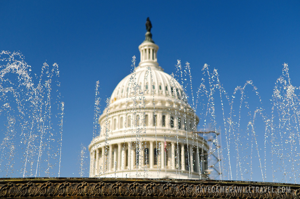 The US Capitol Dome seen through the water fountains above the new US Capitol Visitors Center. Shallow depth of field--focus on the water fountain
