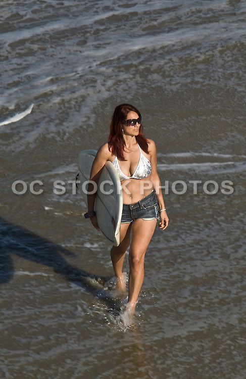 Woman Walking On The Beach With Surf Board