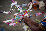 A man makes an adjustment to a headdress during a celebration at a village in Madang Province, Papua New Guinea on July 26, 2017. While the headdress is an old tradition in the country, the inclusion of snack food packaging is a more recent addition.