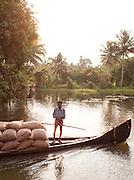A man transports sacks of rice on his canoe in the Kerala Backwaters, near Alappuzha, India