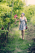A young woman in a summer dress goes for a walk in the countryside.
