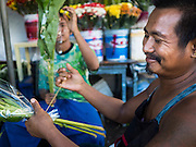 """11 JUNE 2015 - MAHACHAI, SAMUT SAKHON, THAILAND:  Burmese migrant workers who work in a florist shop package flowers in Samut Sakhon. Labor activists say there are about 200,000 migrant workers from Myanmar (Burma) employed in the fishing and seafood industry in Mahachai, a fishing port about an hour southwest of Bangkok. Since 2014, Thailand has been a Tier 3 country on the US Department of State Trafficking in Persons Report (TIPS). Tier 3 is the worst ranking, being a Tier 3 country on the list can lead to sanctions. Tier 3 countries are """"Countries whose governments do not fully comply with the minimum standards and are not making significant efforts to do so."""" After being placed on the Tier 3 list, the Thai government cracked down on human trafficking and has taken steps to improve its ranking on the list. The 2015 TIPS report should be released in about two weeks. Thailand is hoping that its efforts will get it removed from Tier 3 status and promoted to Tier 2 status.       PHOTO BY JACK KURTZ"""