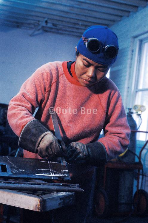A woman welder working on metal