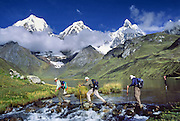 """Trekkers cross the outlet stream of Lake Carhuacocha (13,600 feet) in the Cordillera Huayhuash, Andes Mountains, Peru, South America. On the left, Yerupaja Grande (east face, 6635 m or 21,770 ft) is the second-highest peak in Peru, highest in Cordillera Huayhuash, and highest point in the Amazon River watershed. At center is Yerupaja Chico (20,080 feet). On right is Mount Jirishanca (""""Icy Beak of the Hummingbird,"""" 6126 m or 20,098 feet)."""