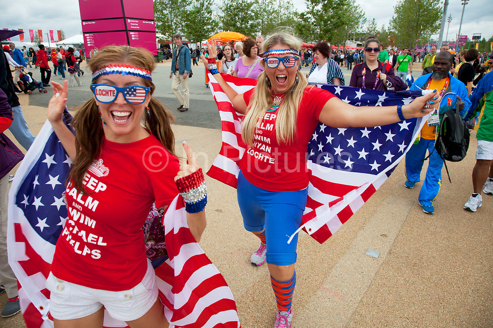 London 2012 Olympic Park in Stratford, East London. Fans of Team USA are abundant at the park. Wearing stars and stripes, the flag of America is a common sight. These girls are particularly proud to be wearing red white and blue.