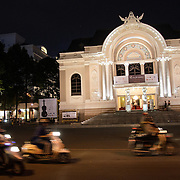 Scooters rush past in front of the Saigon Opera House in Ho Chi Minh City, Vietnam.