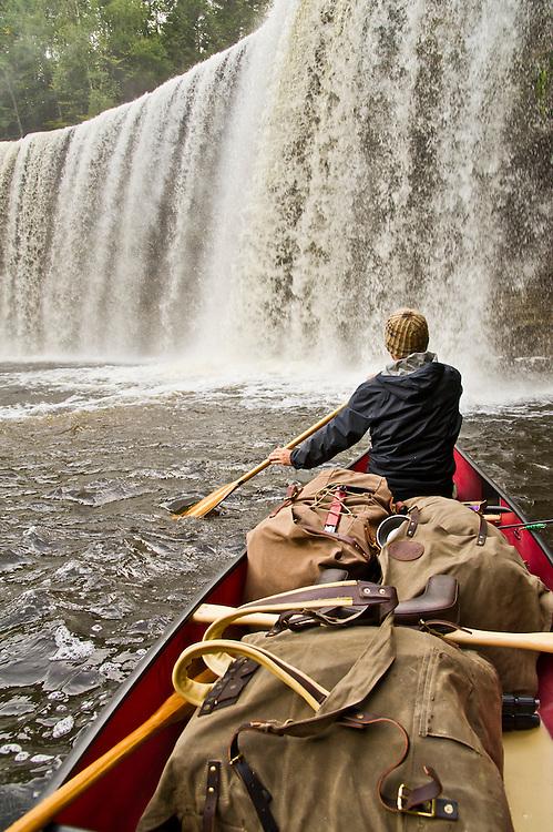 Paddling a canoe near the Upper Falls of the Tahquamenon River at Tahquamenon Falls State Park near Newberry Michigan.