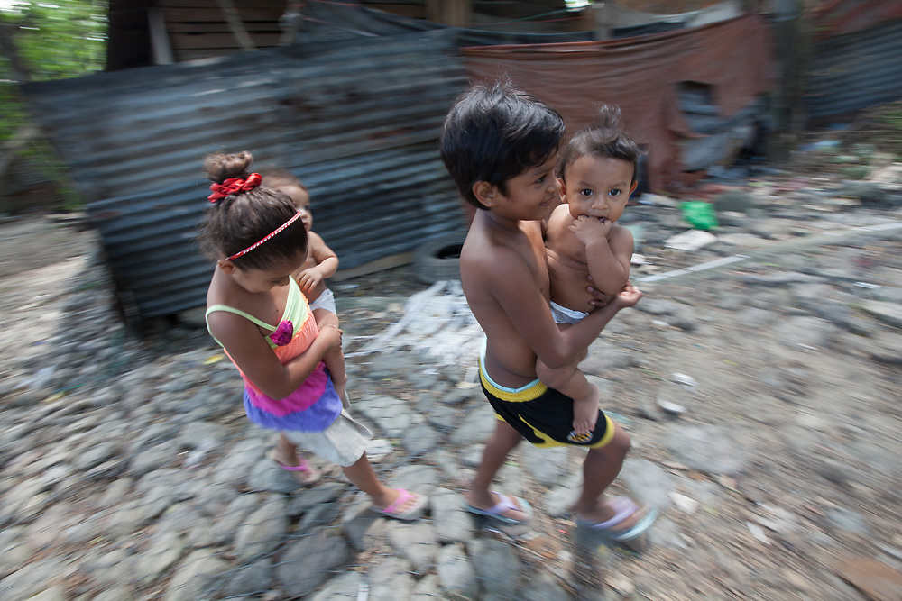 Rivera Hernández, on the outskirts of San Pedro Sula, is known for being extremely violent and dangerous. Unemployment and poverty, are thought to be even more important factors in the wave of migrations to the US than the violence that affects the area. Here two girls carry their baby sisters through the neighbourhood.