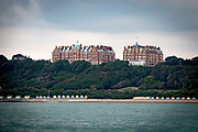 The iconic buildings of Metropole and The Grand buildings stand on The Leas at the top of Radnor Cliff tree lined hill, below is the Lower Leas Coastal Park and along the  Mermaid beach front are colourful Sandgate beach huts photographed from the sea in Folkestone, Kent, England, United Kingdom.