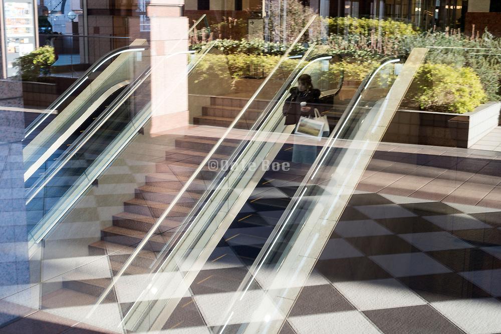 indoors escalator and outdoors window reflection Tokyo Japan