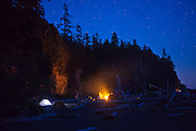 Hikers keep warm by a campfire at night on Tsusiat Beach, West Coast Trail, British Columbia, Canada.