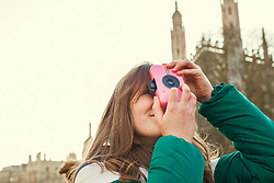 Young Woman Taking a Photograph outdoors, Cambridge, England, United Kingdom