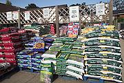 Bags of compost fertiliser piled on pallets in a garden centre, Woodbridge, Suffolk, England