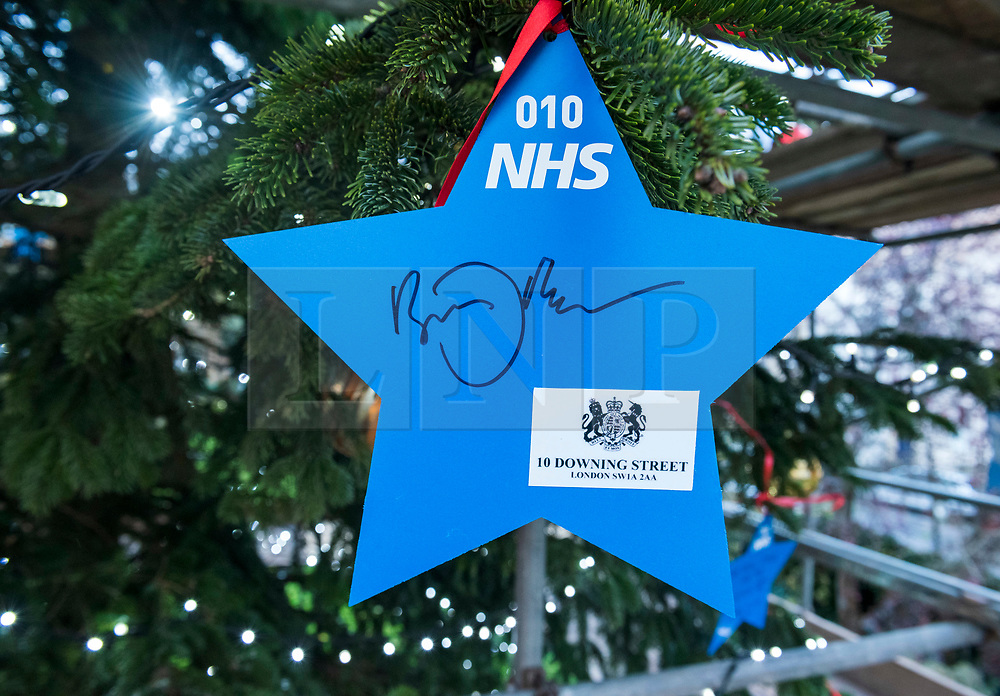 """© Licensed to London News Pictures; 17/11/2020; Bristol, UK. A star signed by the Prime Minister BORIS JOHNSON is placed on a giant Christmas tree for the """"Florence NHS Christmas Tree"""" Thank You NHS Stars Fundraiser, with blue stars signed by among others the UK Prime Minister Boris Johnson, Health Secretary Matt Hancock and Deputy Chief Medical Officer Jonathan Van-Tam. For the 10th year Clifton Village in Bristol has a 50ft illuminated Christmas tree, the tallest in any UK village. Photo credit: Simon Chapman/LNP."""