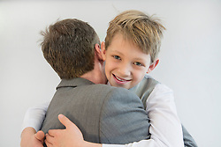 Father and son embracing each other, smiling, close up
