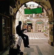 Silhouette of a porter sitting in the old city of Damascus, Syria