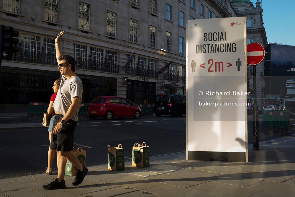 With a further 149 reported dying from Coronavirus in the last 24hrs, taking the UK death toll to 43,320, a Londoner hails a taxi next to social distance advice rules on Regent Street during the Covid pandemic, on 25th June 2020, in London, England.
