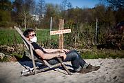 """Porträt von einem Mann mit einer Maske, der auf einem Liegestuhl sitzt, an einem Ort namens """"Corona-Strand"""" in Zeiten sozialer Distanz. @rischaard"""