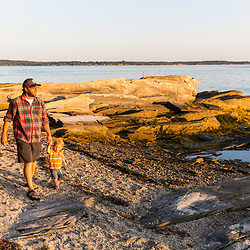 A man and his young son explore the shoreline on East Gosling Island in Casco Bay, Harpswell, Maine.