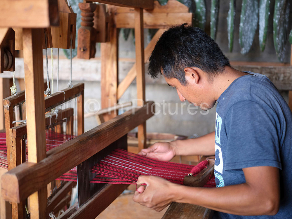 Juan Carlos weaving a scarf using merino wool dyed with cochineal on a 4-shaft loom in the Zapotec village of Teotitlan del Valle, Oaxaca, Mexico on 26 November 2018