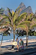 Beach goers walk along Ipanema beach past Two Brothers Mountain early morning in Rio de Janeiro, Brazil.
