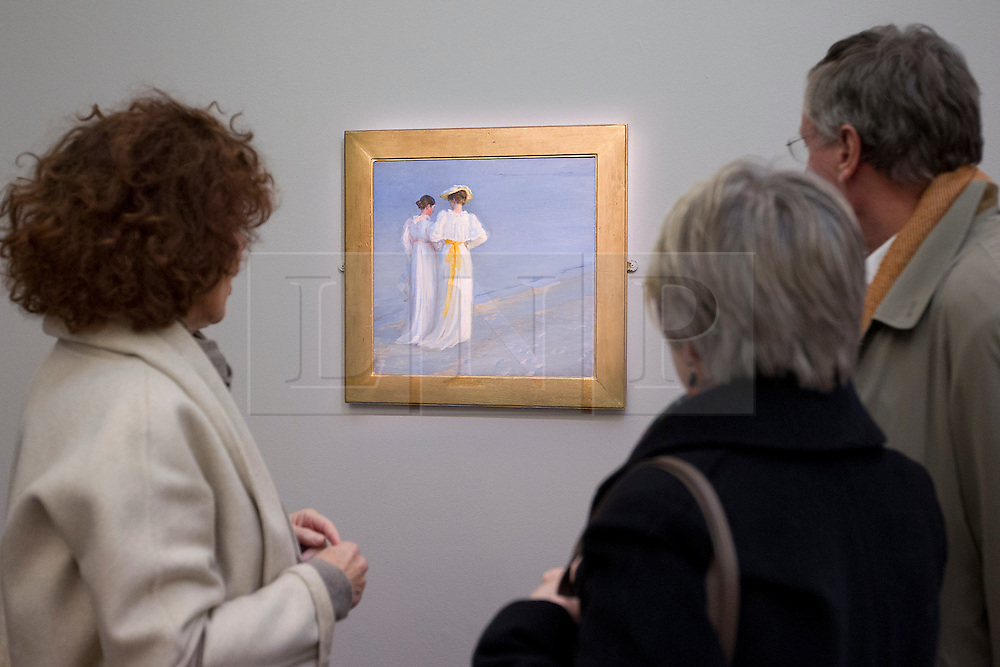 © Licensed to London News Pictures. 16/11/2012. London, UK. Visitors to Sotheby's New Bond Street auction house look at 'Summer Evening on Skagen's South Beach' (1893) (est. GB£150,000-250,000), an oil study by Danish artist Peder Severin Kroyer, at a press call in London today (16/11/12).  The sale, featuring works by 19th century European painters, is set to take place on the 20th of November. Photo credit: Matt Cetti-Roberts/LNP