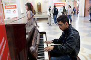 Brazilian Man playing a piano in public, this is an experimental project funded by the city council, to encourage more interaction with public spaces such as train stations, a similar scheme has been tried in London and other cities, but it orinigated in Brazil. Luz Station, Sao Paulo, Brazil.