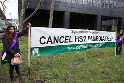 London, UK. 12th January, 2018. Activists stand holding an anti-HS2 banner in Euston Square Gardens. Local residents and environmental campaigners are protesting against the planned felling of mature London Plane, Red Oak, Common Whitebeam, Common Lime and Wild Service trees in Euston Square Gardens to make way for temporary sites for construction vehicles and a displaced taxi rank as part of preparations for the HS2 high-speed rail line.