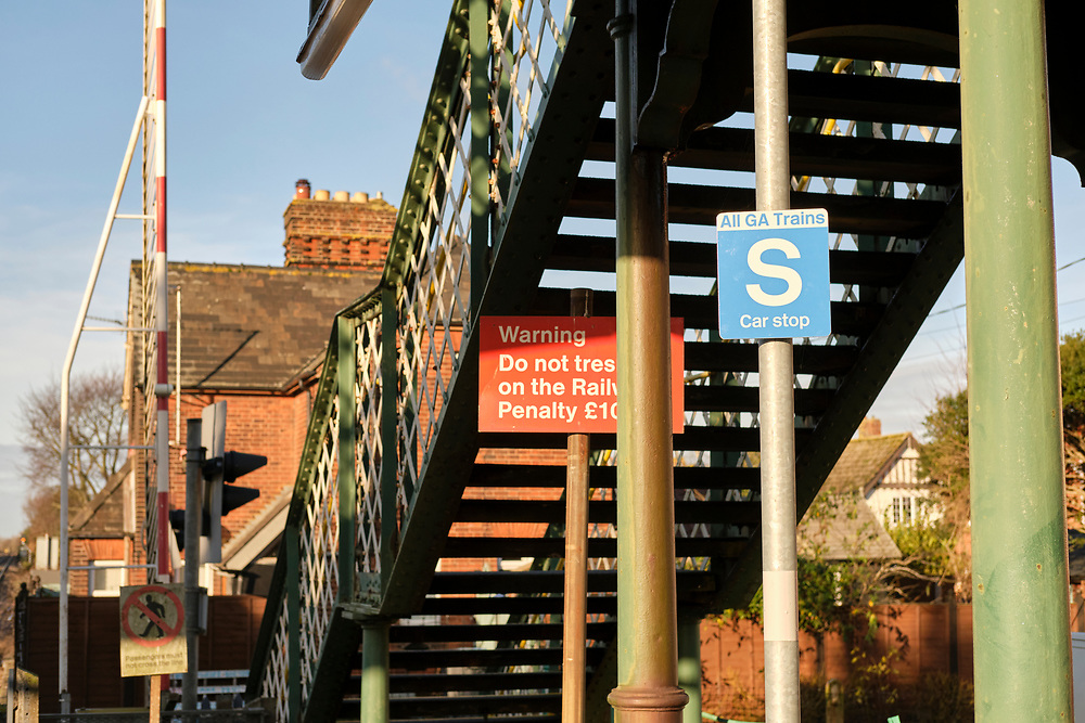 Close up of car Stop sign at the end of the platform at Trimley Station. The footbridge allows people to walk over the line when the level crossing is closed.<br /> <br /> Photo by Jonathan J Fussell, COPYRIGHT 2020