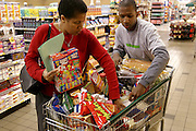 (MODEL RELEASED IMAGE). Brandon, who's off from school this week, accompanies Rosemary Revis to shop for their week's worth of food for the food portrait at the Harris Teeter supermarket, a short drive from their suburban home in Raleigh, North Carolina. (Supporting image from the project Hungry Planet: What the World Eats.)