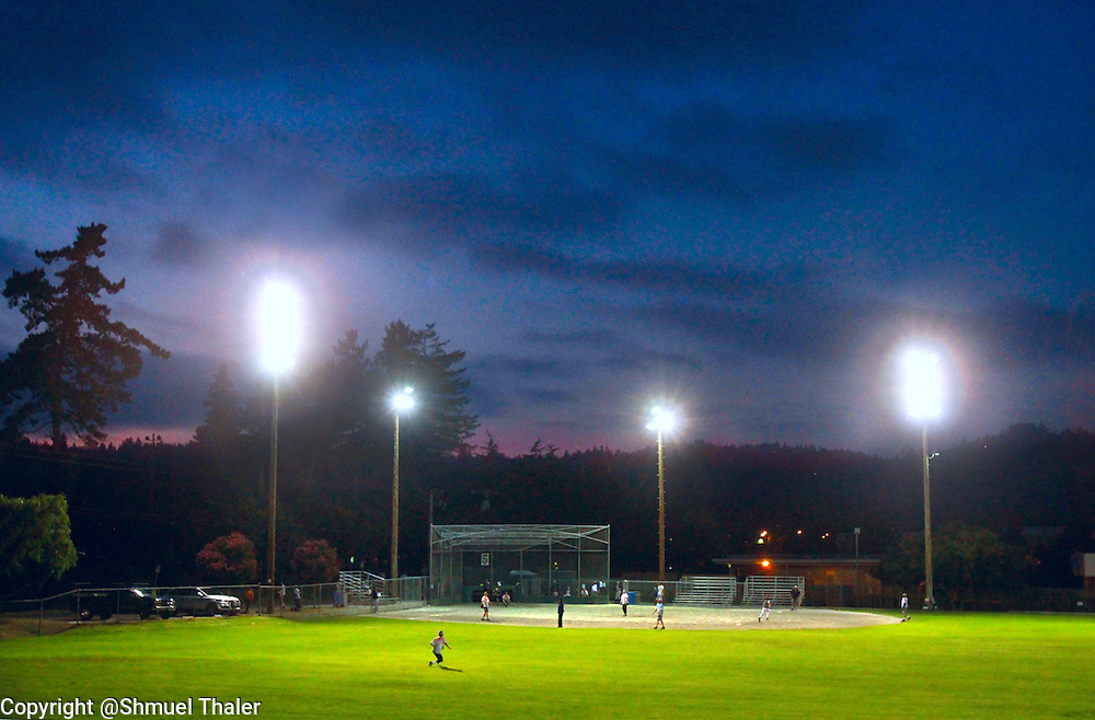The field lights shine through the gathering darkness at Harvey West Park in Santa Cruz, California as the boys of summer take to their field of dreams during a men's softball league game.<br /> Photo by Shmuel Thaler <br /> shmuel_thaler@yahoo.com www.shmuelthaler.com